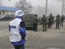 An OSCE observer and Ukrainian military personnel in Mariupol, 24.01.2015; Source: dpa-picturealliance